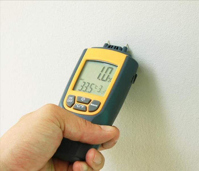 yellow moisture meter penetrating a wall