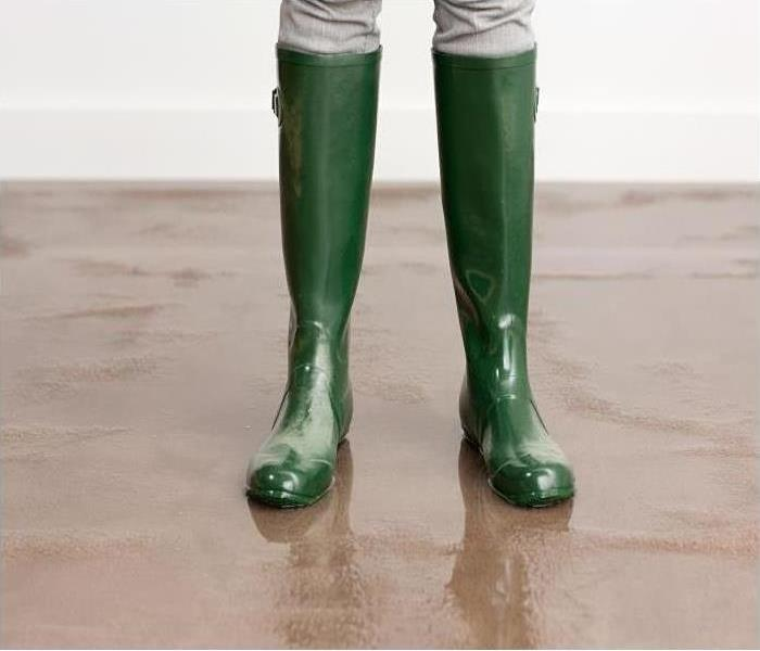 A person with green rain boots on standing on wet carpet.