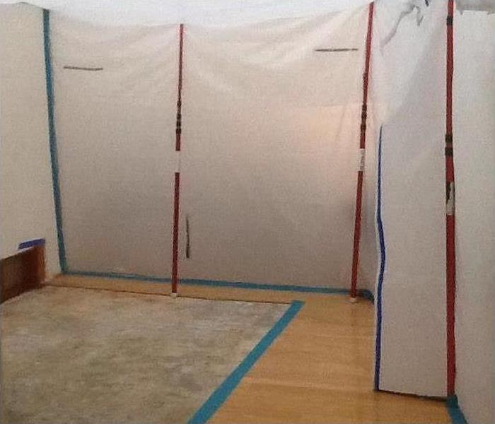 Room with wood floors and plastic sheeting hung with blue and red tape