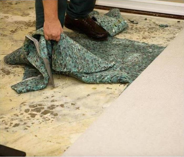 A man pulling carpet padding up from a base board.