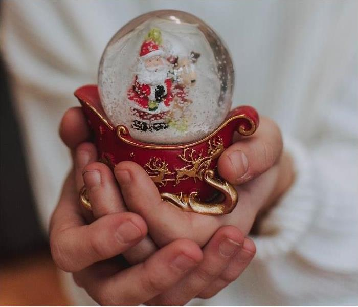 person with sleigh snowglobe in hand